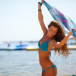 Beautiful woman in a bathing suit standing on the beach at sunse - Foto Stock