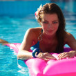 Young beautiful woman relaxing in a pool - Stock Photo