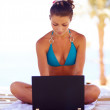 Royalty-Free Stock Photo: Beautiful woman on the beach with a laptop computer enjoying li
