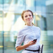 Pretty young business woman with newspaper using mobile phone - Stock Photo
