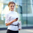 Pretty young business woman with newspaper using mobile phone - Stock fotografie