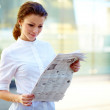 Young beautiful business woman reading newspaper - Stock Photo