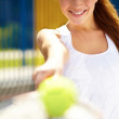 Portrait of a young female tennis offering you the ball - Lizenzfreies Foto