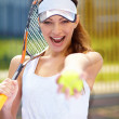 Portrait of a young female tennis player holding her racquet and - Stock Photo