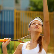 Young female tennis player getting ready to serve the ball - Stock Photo