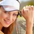 Portrait of a young female tennis player with racquet - Stock Photo