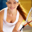 Portrait of a young tennis player standing ready for a serve - Stock Photo