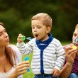 Attractive Young Parents Having Fun Blowing Bubbles with their Child Boy in the Park - Stock Photo