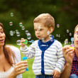 Royalty-Free Stock Photo: Attractive Young Parents Having Fun Blowing Bubbles with their Child Boy in the Park
