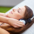 Beautiful woman with headphones posing while lying on sunbed - Stock Photo