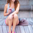Royalty-Free Stock Photo: Young woman relaxing outside and drinking coffee