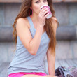 Young woman relaxing outside and drinking coffee - Stock Photo