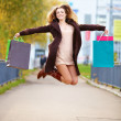 Happy woman with shopping bags and jumping - Stock Photo