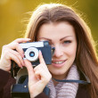 Pretty woman focusing lens on vintage camera - 图库照片