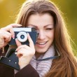 Pretty woman focusing lens on vintage camera - Zdjęcie stockowe
