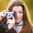 Pretty woman focusing lens on vintage camera - Stok fotoğraf