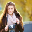 Woman standing with vintage camera outdoor - Foto Stock