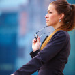 Businesswoman standing in front office buildings - Stock Photo