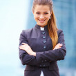 Businesswoman standing in front of cityscape - Stock Photo