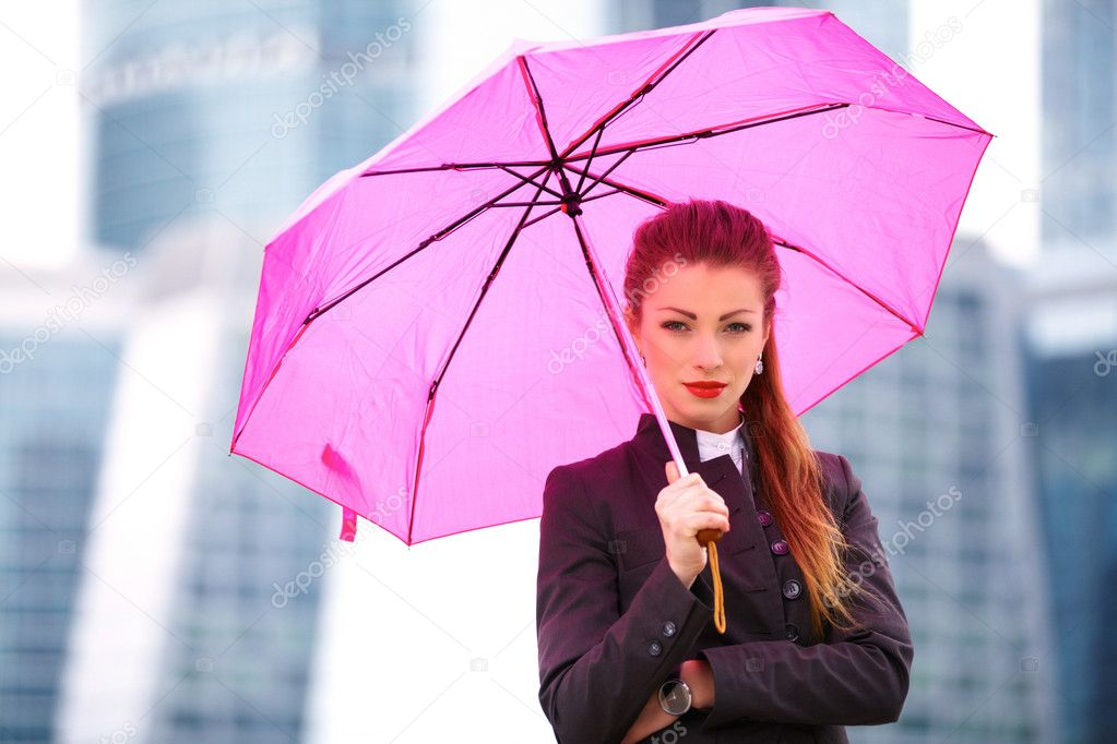 Young business woman with pink umbrella outdoor — Stock Photo #14756943