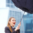 Woman with umbrella fighting with strong wind - Stock Photo