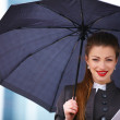 Business woman with digital tablet and umbrella - Stock Photo