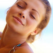 Portrait of cheerful woman enjoying sun and sea at beach - Stockfoto