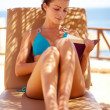 Pretty young female reading a book while lying by the beach - Stockfoto