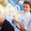 Young business woman with documents sitting on stairs - Stockfoto