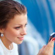 Young businesswoman using mobile phone over building background - Stockfoto