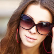 Portrait of happy young woman winking over her sunglasses at you - Stockfoto