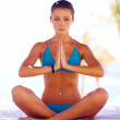 Young beautiful woman on the beach making yoga - Stock Photo