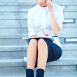 Young businesswoman sitting on stairway on cell phone - Stock Photo