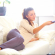 Happy young woman watching tv on sofa - Foto de Stock