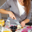 Woman making salad in kitchen smiling - Foto de Stock
