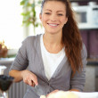 Woman making salad in kitchen smiling - Stok fotoğraf