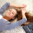 Happy young woman lying on floor with laptop - Stok fotoğraf
