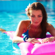Very happy woman no pink air bed in swimming pool - Stok fotoğraf