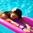 Very happy woman no pink air bed in swimming pool - Zdjęcie stockowe