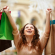 Happy young woman with shopping bags at mall - Stock Photo