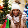 Royalty-Free Stock Photo: Young with shopping bags and christmas tree