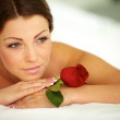 Beautiful woman in spa salon with red rose - Stock Photo