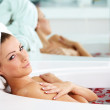 Young woman lying in bath tub with rose petals - Stock Photo