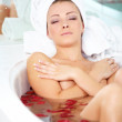 Young woman lying in bath tub with her eyes closed - Stock Photo