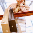 Woman after shopping and holding bags at the mall - Stock Photo