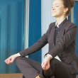 Royalty-Free Stock Photo: Business woman doing yoga at the office