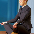 Business woman doing yoga at the office - 