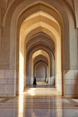 Muslim woman walking through arches — Stock Photo