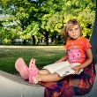 Young girl learning and reading a book in park — Foto de Stock