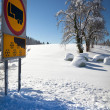 Traffic sign warns of snow and ice, on sunny and snowy day, with — Stock Photo